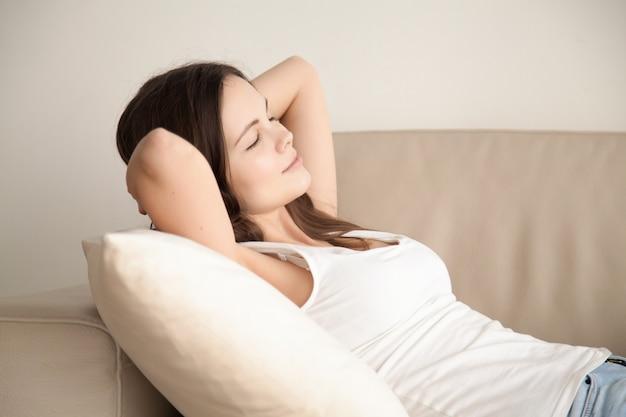 Mujer joven que descansa sobre el sofá cómodo en casa