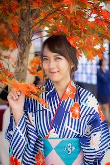 Mujer joven que desgasta el kimono tradicional japonés en color del otoño. japón