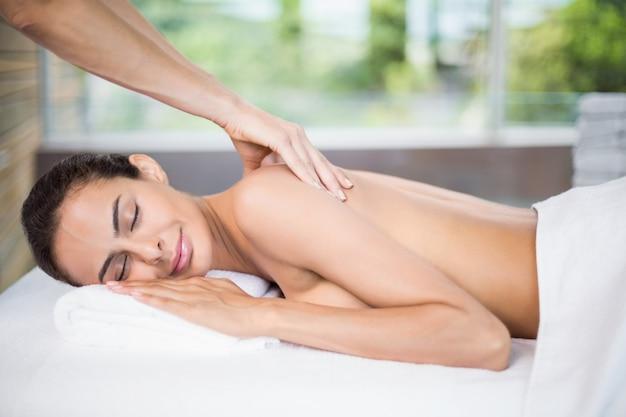 Mujer joven que disfruta de masaje de espalda