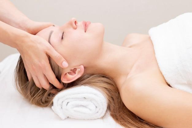 Mujer joven que disfruta de masaje en salón del balneario. masaje facial. primer de la mujer joven que consigue el tratamiento del masaje del balneario en el salón del balneario de la belleza. cuidado de la piel y del cuerpo de spa. tratamiento de belleza facial. cosmetología.