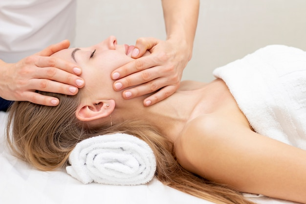 Mujer joven que disfruta de masaje en salón del balneario. masaje facial. primer plano de mujer joven recibiendo tratamiento de masaje spa en el salón de belleza spa. tratamiento de belleza facial. cosmetología.