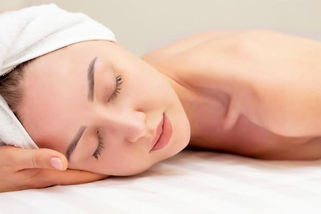 Mujer joven que disfruta de masaje en salón del balneario. primer de la mujer joven que consigue el tratamiento del masaje del balneario en el salón del balneario de la belleza. cuidado de la piel y del cuerpo de spa. tratamiento de belleza facial. cosmetología.