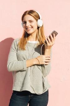 Mujer joven que disfruta de la música en el auricular a través de teléfono inteligente contra el fondo rosa