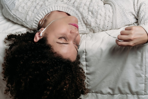 Mujer joven que disfruta de música en cama