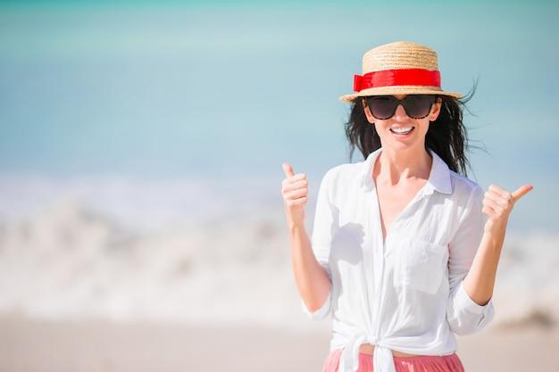 Mujer joven que disfruta del sol tomando el sol por el océano turquesa perfecto. chica levanta los pulgares al aire libre
