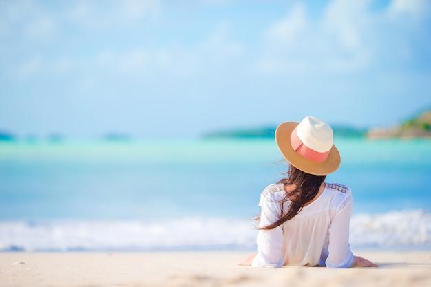 Mujer joven que disfruta del sol tomando el sol por el océano turquesa perfecto.