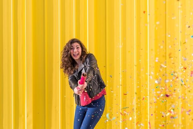 Mujer joven que se divierte con confeti sobre amarillo. al aire libre. concepto de diversión y estilo de vida.