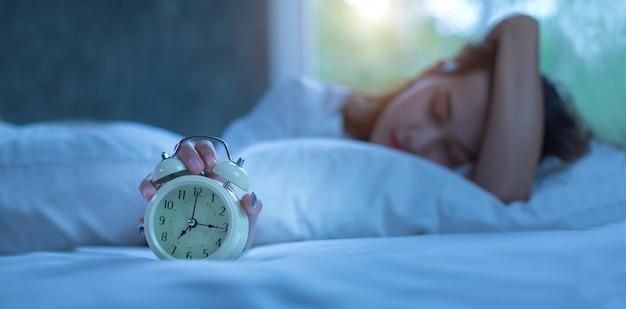 Mujer joven que duerme en cama con la alarma en la noche