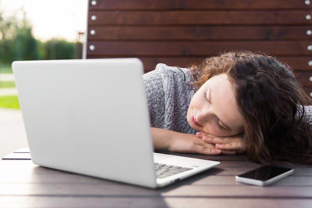 Mujer joven que duerme con el cuaderno en la tabla en un parque