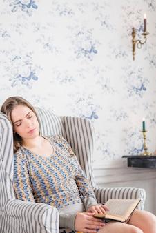 Mujer joven que duerme en el sillón con el libro en sus manos
