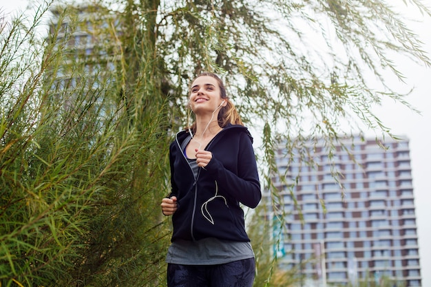 Mujer joven que se ejecuta en el entorno urbano