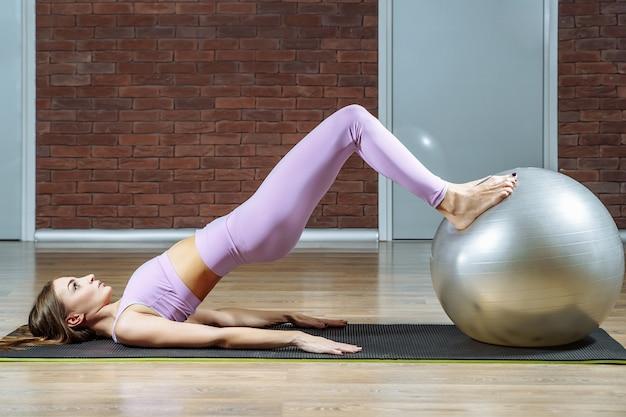 Mujer joven que ejercita con la bola de la aptitud en gimnasio