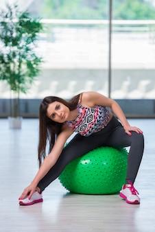 Mujer joven que ejercita con la bola suiza en concepto de la salud