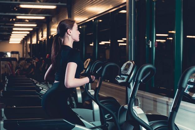 Mujer joven que ejercita en la máquina cardio elíptica