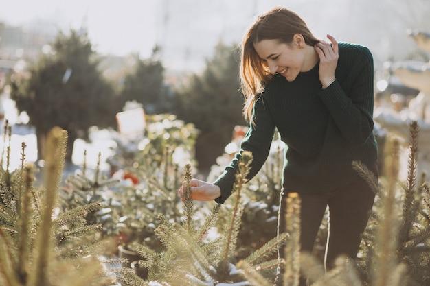 Mujer joven que elige un árbol de navidad en un invernadero