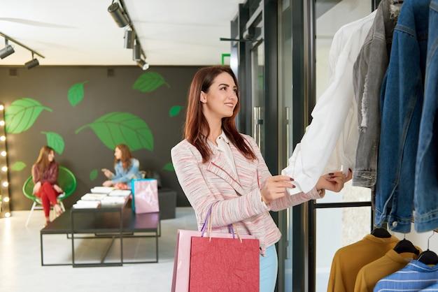 Mujer joven que elige la chaqueta para comprar en ella hace compras.