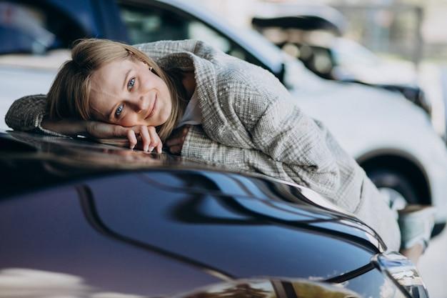 Mujer joven que elige un coche en una sala de exposición de automóviles