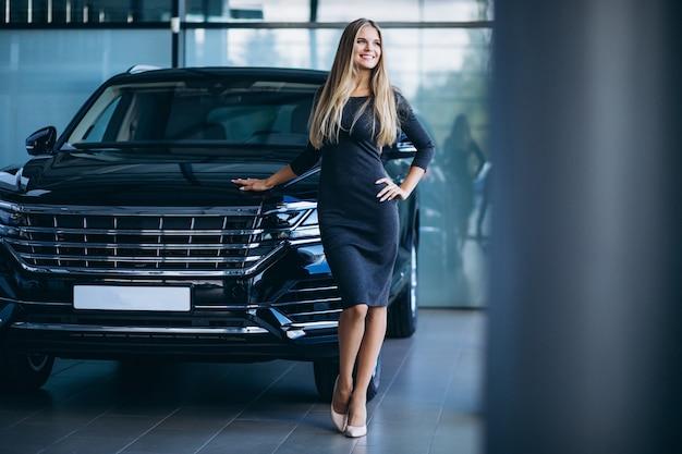 Mujer joven que elige un coche en un showroom de automóviles