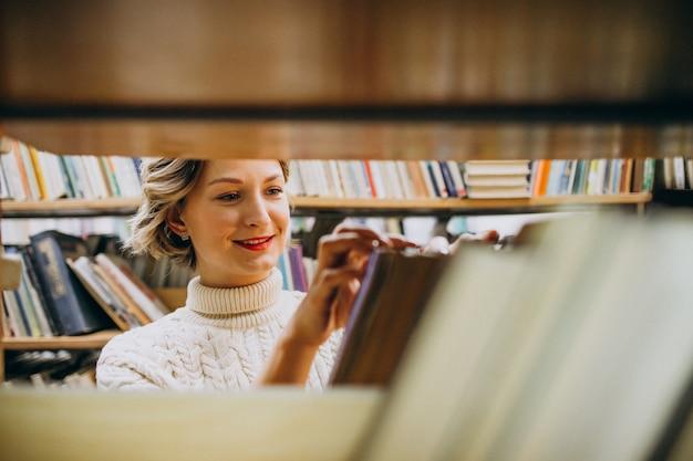 Mujer joven que elige el libro en la biblioteca