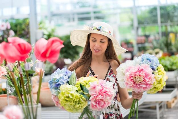 Mujer joven que elige un manojo de hortensias frescas