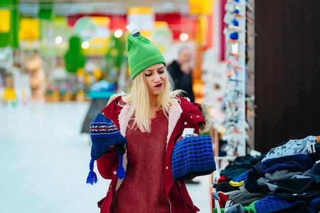 Mujer joven que elige el sombrero en centro comercial