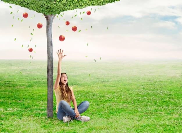 Mujer joven que es sorprendido por una manzana roja debajo de un árbol