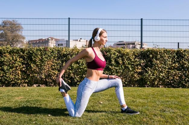 Mujer joven que escucha la música en el auricular que estira sus piernas en el parque