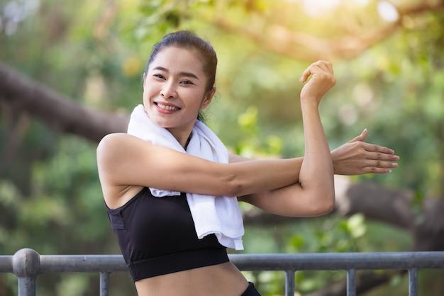 Mujer joven que estira el cuerpo después de trotar, mujer milenaria deportiva feliz corriendo