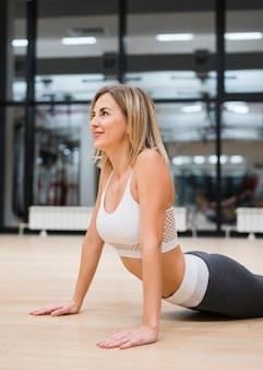 Mujer joven que estira en el gimnasio