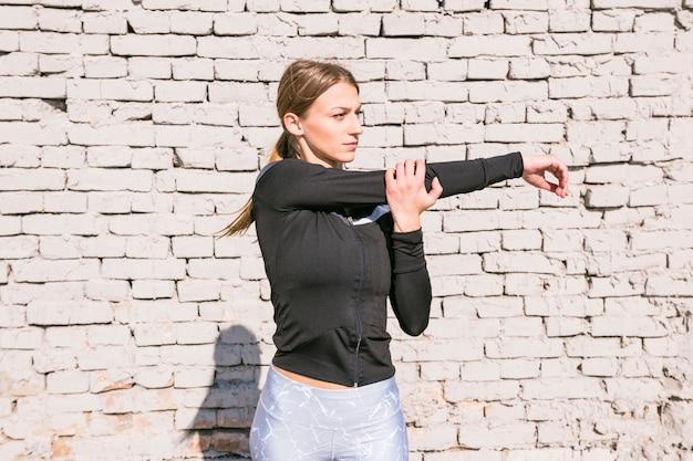 Mujer joven que estira su mano que se coloca delante de la pared de ladrillo blanca