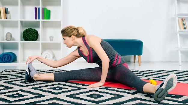 Mujer joven que estira su pierna mientras está sentado en la sala de estar