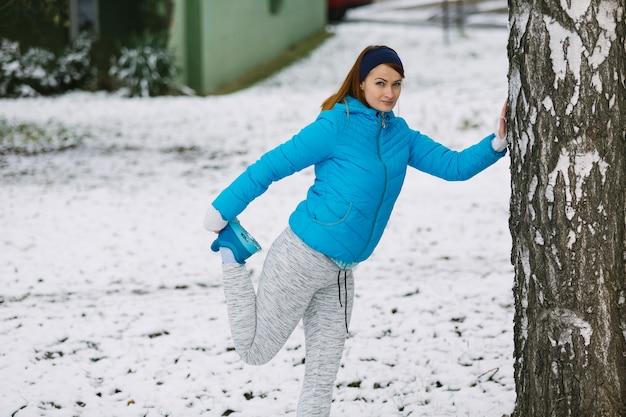 Mujer joven que estira su pierna de pie cerca del árbol