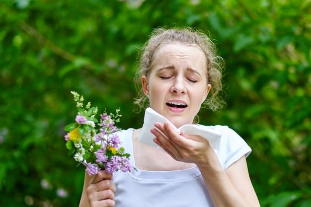 Mujer joven que estornuda con el ramo de flores. concepto: alergia estacional.