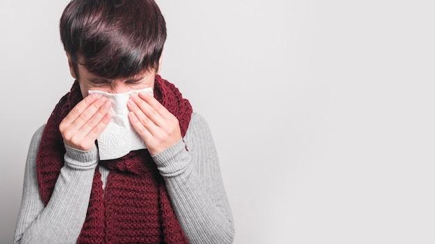 Mujer joven que estornuda en tejido contra fondo gris