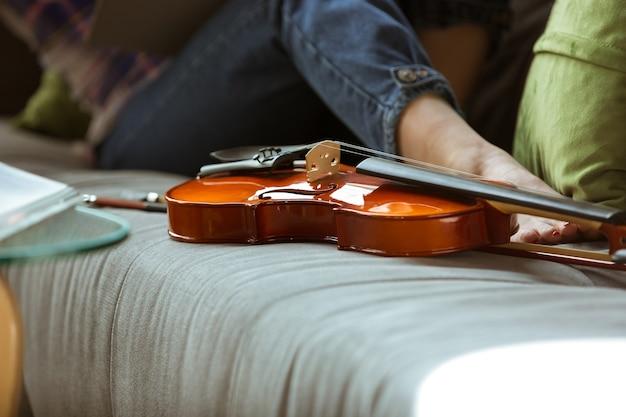 Mujer joven que estudia en casa durante cursos en línea o información gratuita por sí misma. se convierte en músico, violinista mientras está aislado, cuarentena contra la propagación del coronavirus. usando computadora portátil, teléfono inteligente.