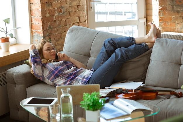 Mujer joven que estudia en casa durante cursos en línea o información gratuita sola