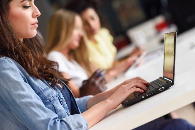 Mujer joven que estudia con la computadora portátil en el escritorio blanco. Foto gratis