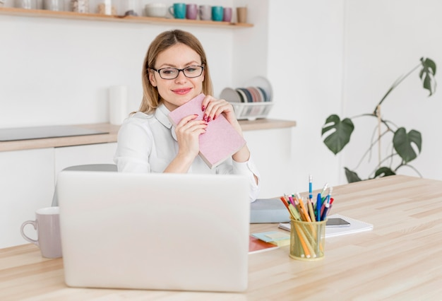 Mujer joven que estudia en la computadora portátil