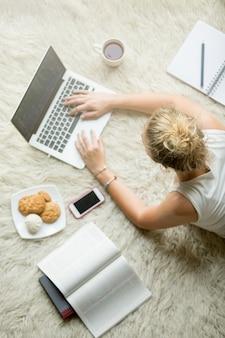 Mujer joven que estudia usando tecnología