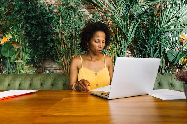 Mujer joven que examina el documento con el ordenador portátil en la tabla de madera