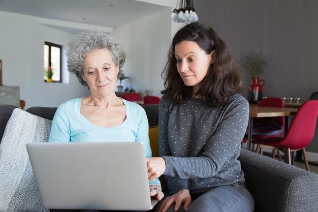 Mujer joven que explica a la abuela cómo utilizar la computadora portátil