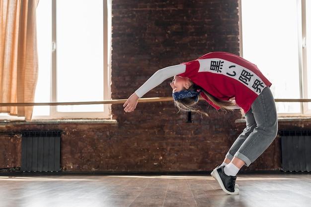 Mujer joven que se extiende hacia atrás en el estudio de danza