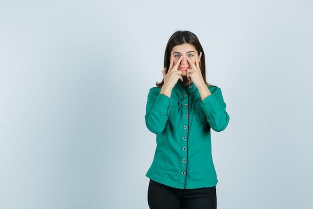 Mujer joven que finge frotar la mascarilla alrededor de la zona de la nariz en camisa verde, pantalones y mirando tranquila, vista frontal.