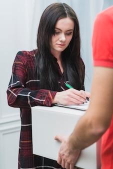 Mujer joven que firma para el paquete cerca del mensajero