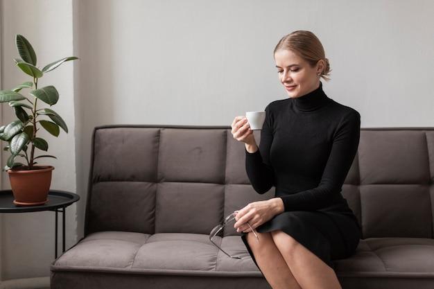 Mujer joven que goza de la taza de café