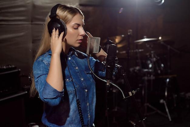 Mujer joven que graba una canción en el estudio.
