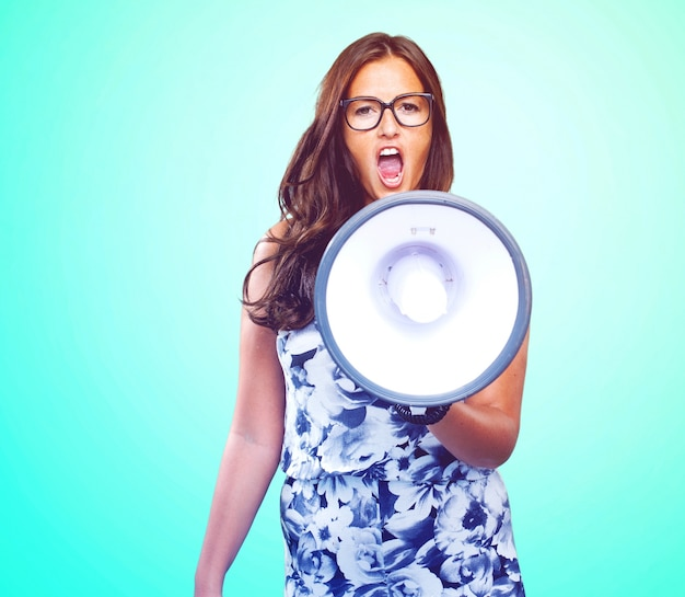 Mujer joven que grita con el megáfono