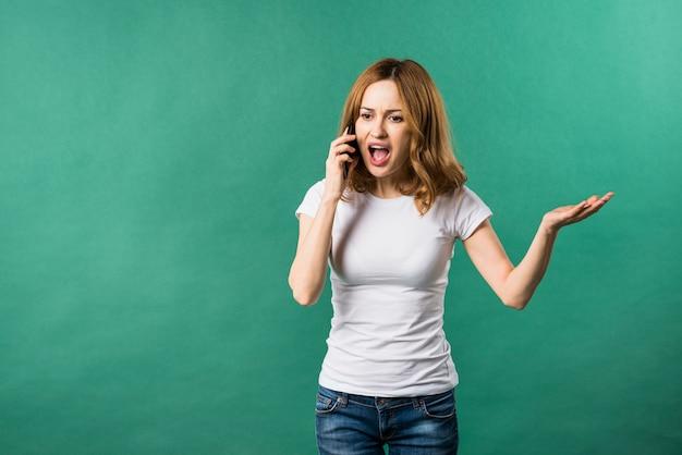 Mujer joven que grita en el teléfono elegante contra el contexto verde
