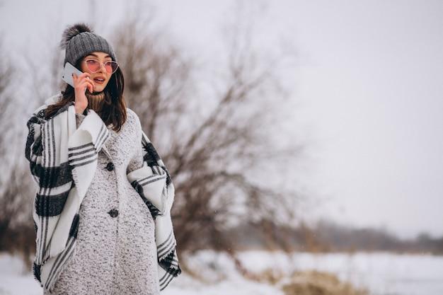 Mujer joven que habla en el teléfono afuera en el parque de invierno