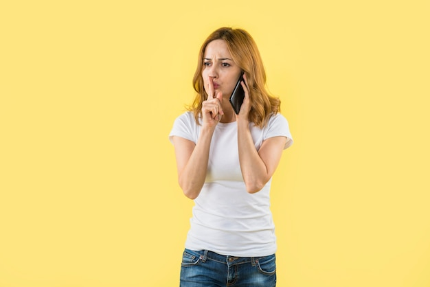 Mujer joven que habla en el teléfono móvil que hace gesto del silencio contra fondo amarillo